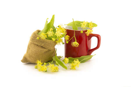 Red cup and small hessian bag of freshly picked yellow linden flowers and leaves, also called tilia and lime, for making a healing tisane or tea over a white background Banque d'images