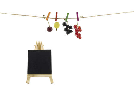 Fresh fruit hanging from clothes pegs on a rope with a fresh cherry, gooseberry, red and black currants and slate chalkboard isolated on white with copy space