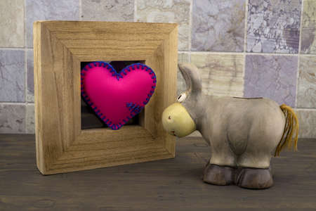 Cute little toy donkey look at handcrafted pink heart in a wooden frame against a tiled background