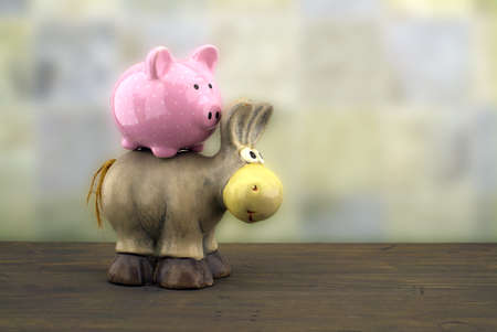 Cute little piggy bank and toy donkey close up side view against a blurred background 版權商用圖片