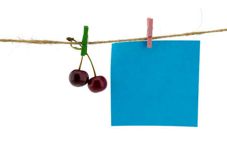 Fresh fruit and and blank sticky note hanging from clothes pegs on a rope with a red cherry and black currants isolated on white with copyspace