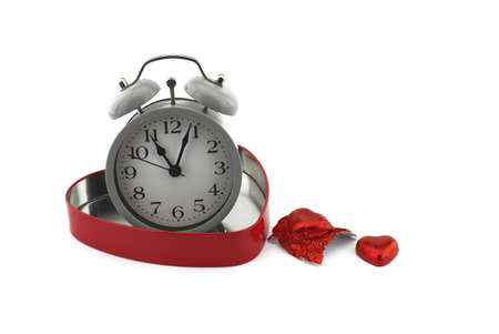 Retro alarm clock in a red heart shaped box with chocolate candy alongside on a white background with copyspace symbolic of love, togetherness and romance for Valentines 版權商用圖片