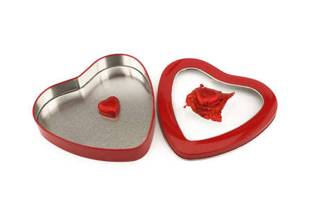 Red heart shaped box with chocolate candy on a white background with copyspace symbolic of love and romance for Valentines
