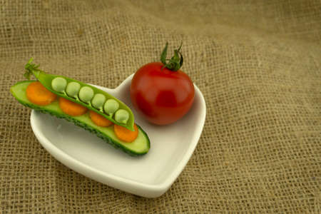 Healthy fresh vegetable sandwich with carrots, peas in a pod and cucumber balance on top of each and red ripe tomato in a heart-shaped plate on jute