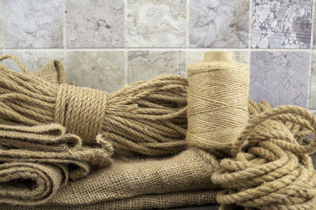 Assorted balls of jute twine, sackcloth fabric and string with skeins of rope in a close up rustic still life