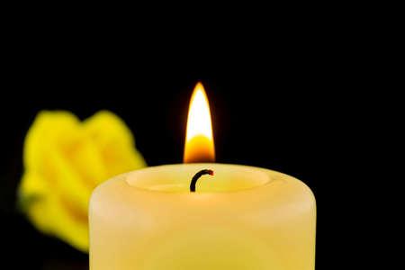Single burning yellow candle next to rose against dark background