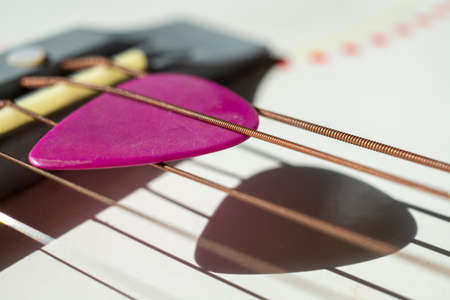 Colorful pink plectrum in guitar strings in a close up oblique angle view in a music and entertainment concept 版權商用圖片