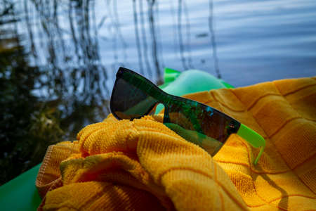 Sunglasses on a yellow towel placed on a green inflatable mattress floating on water in a concept of a summer vacation