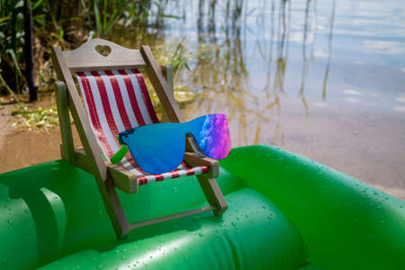 Sunglasses on a small striped deck chair balanced on a wet green inflatable mattress floating on water in a concept of a summer vacation