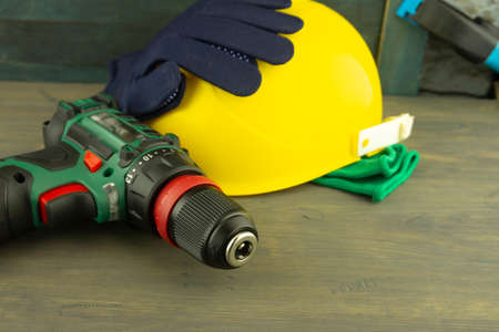 Cordless drill and yellow protective helmet and pairs of new blue gloves on a workbench, blurred in background. Construction tools and work equipment in close-up with copy space