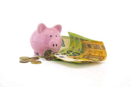 Euro banknotes and loose coins with a little ceramic pink piggy bank over a white background with copyspace for savings, finances or money related themes 版權商用圖片