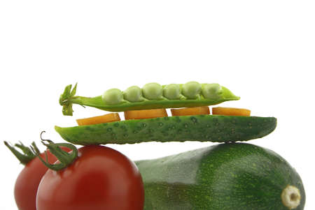 Healthy fresh vegetable still life over white with ripe red tomatoes, courgette or zucchini, carrots, peas in a pod and cucumber balance on top of each other 版權商用圖片