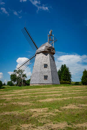 Old windmill in grassland in a country landscape with woodland trees under a cloudy blue sky in a scenic landscape 版權商用圖片