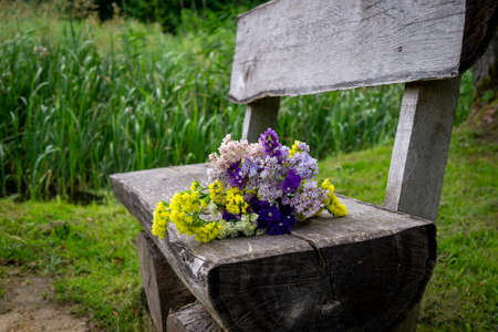 Posy of fresh spring flowers on a rustic weathered wooden bench outdoors in a park with a background of greenery conceptual of the season 版權商用圖片