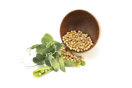 Dried peas spilling from a rustic bowl and fresh plant with pods isolated on a white background