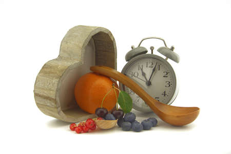 Culinary still life with old-fashioned alarm clock, pot, wooden spoons, cherries and orange, red currants and blueberries over an off white background with copy space 版權商用圖片