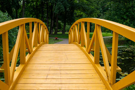 Empty arched wooden pedestrian bridge curving away in a receding perspective outdoors in a park