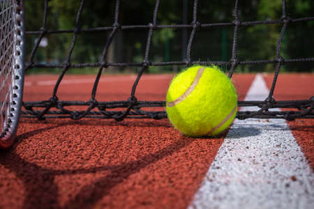 Shadows of racket and net surrounding a tennis ball on a white line on an outdoor court in sunshine in a sport and active lifestyle concept 版權商用圖片