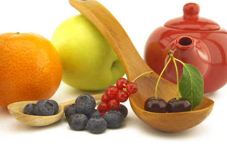 Fresh seasonal fruit still life with assorted berries including blueberries, cherries and red currants on wooden spoons with apple and orange and colorful red teapot 版權商用圖片