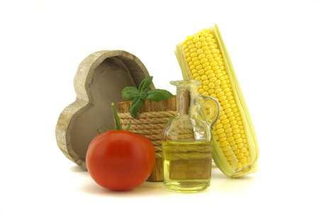 Healthy vegetables including a juicy ripe red tomato and fresh corncob with decanter of olive oil and basil plant in a rustic wooden pot with rope over a white background 版權商用圖片