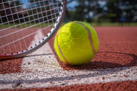 Tennis scene with white line, ball and racquets on red hard court surface Stock Photo