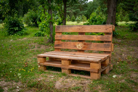 Outdoor furniture made from wood pallets surrounded by trees and greenery in summer sunshine 版權商用圖片