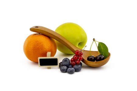 Fresh seasonal fruit still life with small signboard, assorted berries including blueberries, cherries and red currants on wooden spoons with apple and orange on a white background