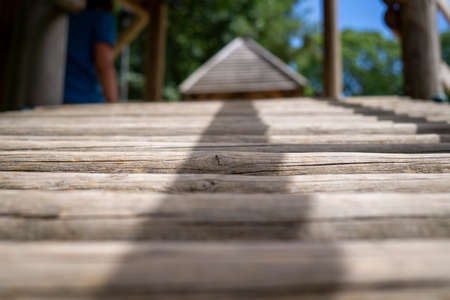 Natural wood climbing frame in a playground in a low angle view along the rungs in an outdoor setting