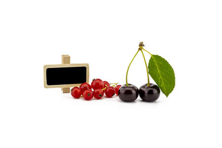 Two ripe cherries with a green leaf and a bunch of red currants and small signboard isolated on a white background
