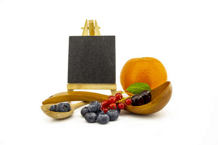 Fresh seasonal fruit still life with small chalkboard and assorted berries including blueberries, cherries and red currants on wooden spoons and orange on a white background