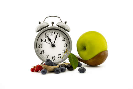 Culinary still life with old-fashioned alarm clock, wooden spoon, cherries, red currants, green apple and blueberries over white background