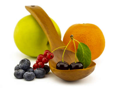 Fresh seasonal fruit still life with assorted berries including blueberries, cherries and red currants on wooden spoons with apple and orange on a white background with copyspace 版權商用圖片