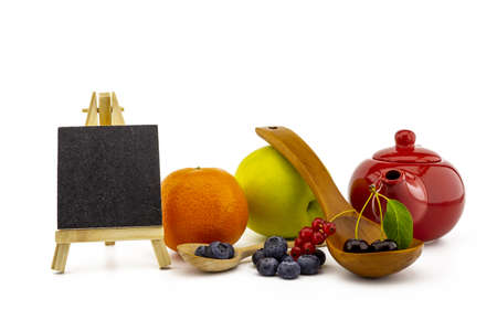 Fresh seasonal fruit still life with small chalkboard and assorted berries including blueberries, cherries and red currants on wooden spoons with apple and orange and colorful red teapot