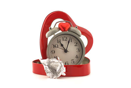 Retro alarm clock in a red heart shaped box with chocolate candy on a white background with copy space symbolic of love, togetherness and romance for Valentines 版權商用圖片