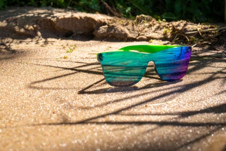 Pair of trendy modern sunglasses with blue mirror lenses on coastal sand in dappled sunshine in a concept of summer with copy space 版權商用圖片
