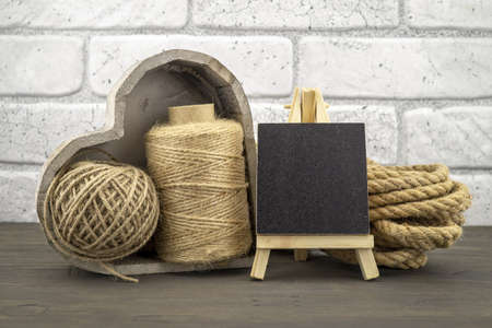 Assorted balls of hemp twine and string with skeins of rope and slate chalkboard in a close up rustic still life 版權商用圖片