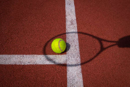Shadows of net and racket surrounding a tennis ball on a white line on an outdoor court in sunshine in a sport and active lifestyle concept 版權商用圖片