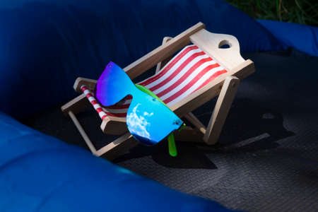 Sunglasses on a small striped deck chair balanced on a blue inflatable mattress in a concept of a summer vacation