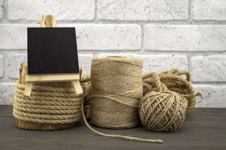 Assorted balls of hemp twine and string with skeins of rope and slate chalkboard in a close up rustic still life Stockfoto