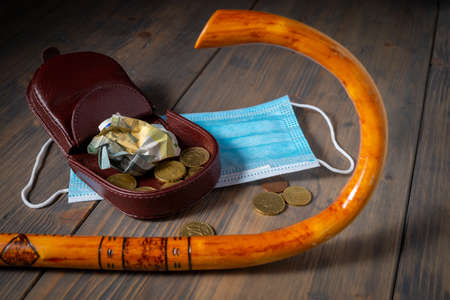 Money spilling from an open purse onto a wooden table with cane and surgical mask alongside viewed from above, old age and pandemic conceptual flat lay still life