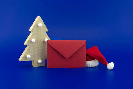 Red envelope for greetings next to a Christmas tree and Santa hat on a festive blue background. New Year and Christmas greeting season concept