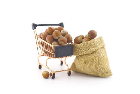 Small hessian bag and shopping cart filled with whole ripe hazelnuts isolated on white background