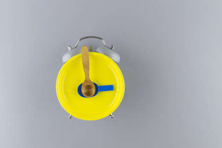 Bright yellow plate on an vintage alarm clock against a gray background. Color of the year and color trends concept 스톡 콘텐츠