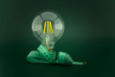 Slimming idea concept with lamp light bulb and measuring tape over a dark green background