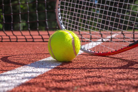 Tennis ball, line and racket on an outdoor court with the racket standing on end casting a shadow across the all weather surface