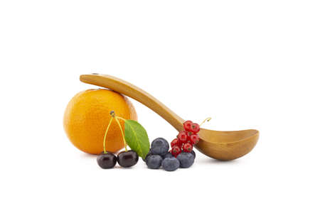 Fresh seasonal berries including blueberries, cherries and red currants, wooden spoon and orange on a white background with copy space