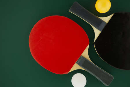 Two table tennis racks with a white and an yellow table tennis ball on green background with free copy space