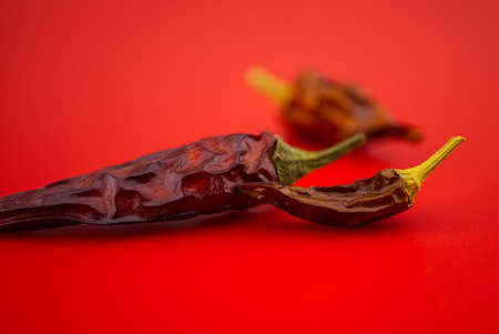 Macro image of dried red chilli pepper on red background