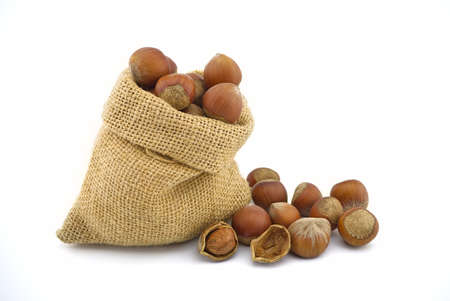 Small hessian bag filled with whole ripe hazelnuts spilling onto a white background