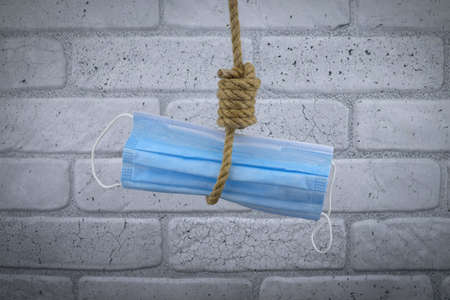 Rope noose around a protective surgical face mask, conceptual of death or mortality during the global virus pandemic against a brick wall background